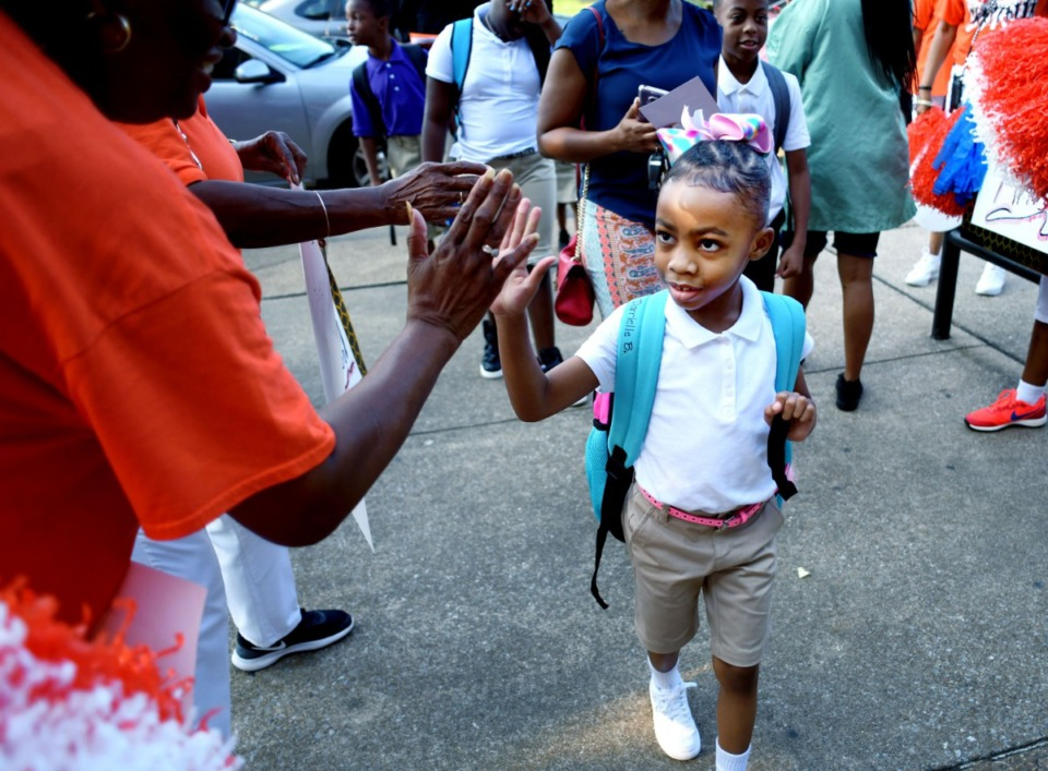 <strong>Darrielle Brown, a 6-year-old first-grader at Dunbar Elementary, is greeted on her first day of school Monday, Aug. 12, by members of the Orange Mound Community Service Center. Dunbar Elementary is an iZone school; with the exception of one pre-K teacher, the teaching and administrative staff are new to the school this year.</strong> (Houston Cofield/Special to the Daily Memphian)