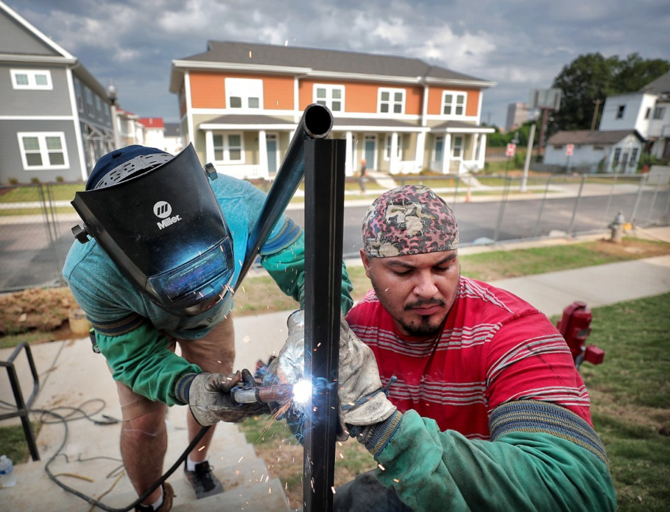 <strong>Eduardo Ardo (left) and Martin Majia construct guard rails at the South City redevelopment on Aug. 6. The nonprofit Women's Foundation for a Greater Memphis has invested $4.7 million in the city's 38126 ZIP code since 2015. The area includes South City.</strong>&nbsp;(Jim Weber/Daily Memphian)