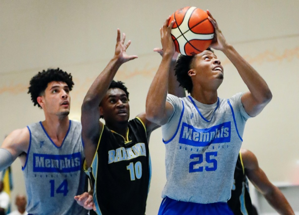 <strong>Tigers forward Jayden Hardaway (right) drives for a layup against NPBA Select defender Ziv Basden (middle) as teammate Isaiah Maurice (left) looks on Thursday in the Bahamas.</strong> (Mark Weber/Daily Memphian)