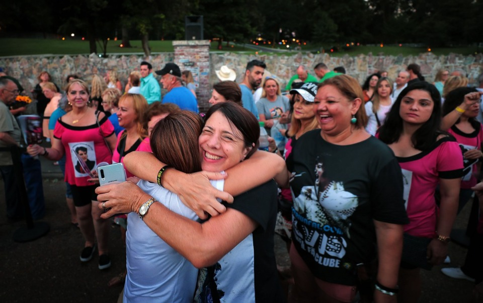 <strong>Valquiria Barbosa (center) of Brazil embraces her friend Fatima Costa as a crowd lines up for the annual Elvis Week vigil in front of Graceland to honor the 42nd anniversary of the King of Rock 'n' Roll's death. Thousands of Elvis Fans old and new gathered at the gates for a procession to Elvis Presley's grave on the grounds of the manor.</strong> (Jim Weber/Daily Memphian)