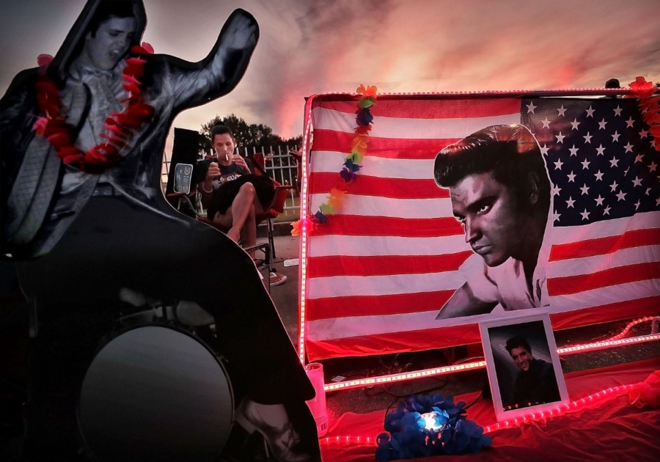 <strong>Marla Pittorf of Buffalo, New York watches the crowd pass by her small Elvis shrine as thousands of Elvis fans old and new gather on the street in front of Graceland during the annual Elvis Week vigil to honor the 42nd anniversary of the King of Rock 'n' Roll's death. A crowd of thousands gathered at the gates for a procession to Elvis Presley's grave on the grounds of the manor.</strong> (Jim Weber/Daily Memphian)