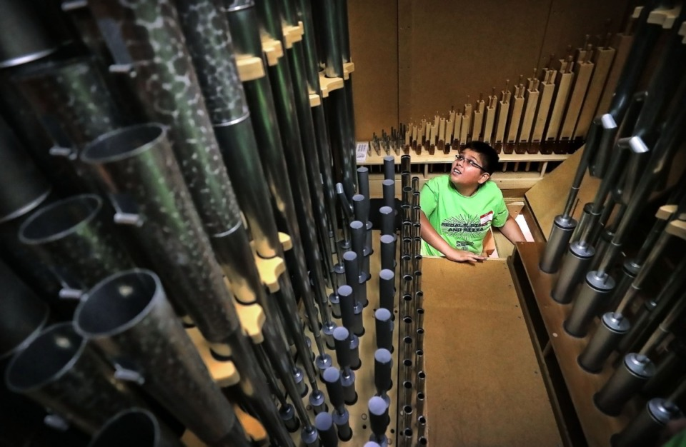 <strong>Issac Neria pokes his head into one of the pipe chambers at St. George's Episcopal Church during a one-day introduction to the pipe organ for young musicians hosted by the Memphis chapter of the American Guild of Organists on Aug. 17, 2019. A group of some 30 musicians got a chance to play pipe organs in two Germantown churches and to explore the guts of the instruments.</strong> (Jim Weber/Daily Memphian)