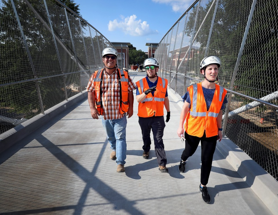 <strong>Jim Lowrance, Josh Jackson and Mary Haizlip walk across the University of Memphis pedestrian bridge Monday, Aug. 12, a few weeks before the long-awaited grand opening.</strong> (Patrick Lantrip/Daily Memphian)