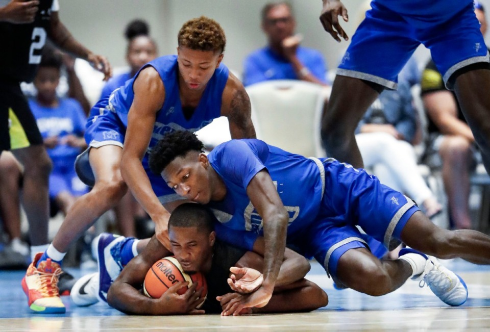 <strong>Memphis Tigers defenders Boogie Ellis (left) and Damion Baugh (right) battle Raw Talent Elite guard Antonio Hanna (middle) for a loose ball during action in their exhibition game in Nassau, Bahamas, Aug. 18, 2019.</strong> (Mark Weber/Daily Memphian)