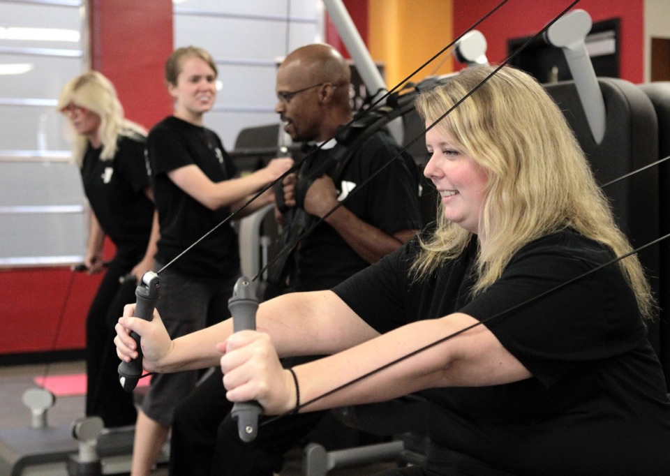 <strong>The Fogelman YMCA, seen here with employee Brenna Walker working out with co-workers on the kinesis functional strength station, received $200,000 from Plough Foundation recently for a renovation that will begin in November.</strong> (Daily Memphian file)