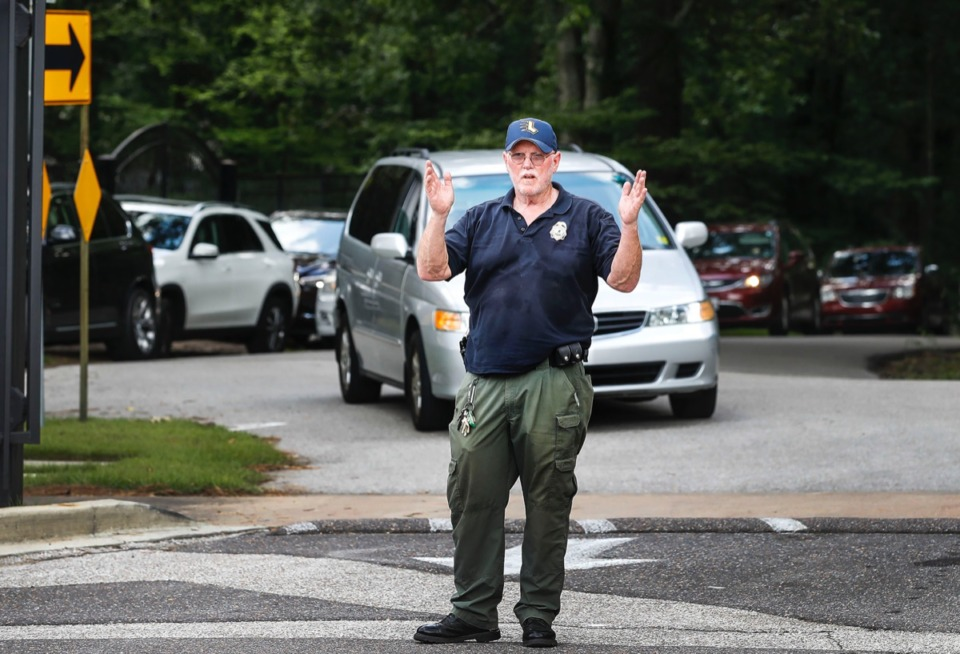 <strong>Lausanne Collegiate School security guard David Frances directs cars lining up to pick up their children on the first day of school Monday, Aug. 12. Lausanne is in a protracted battle with some of its neighbors over crowded car lines after school and lights from football games on the East Memphis campus. </strong>(Mark Weber/Daily Memphian)