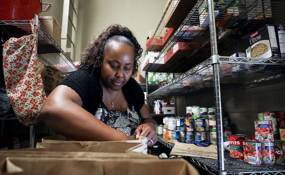 <strong>Linda Webster, director of family enrichment for Neighborhood Christian Center, fills bags of meals for needy families at the organization's North Memphis food pantry at 785 Jackson Ave. on Tuesday, Aug. 20.</strong> (Patrick Lantrip/Daily Memphian)
