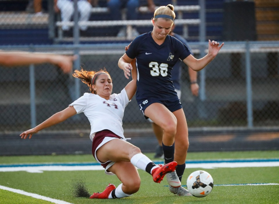 <strong>Collierville mid-fielder Peyton Wilkinson (left) knocks the ball away from Arlington's Maggie Presley during action in their soccer game Aug. 20, 2019.</strong> (Mark Weber/Daily Memphian)