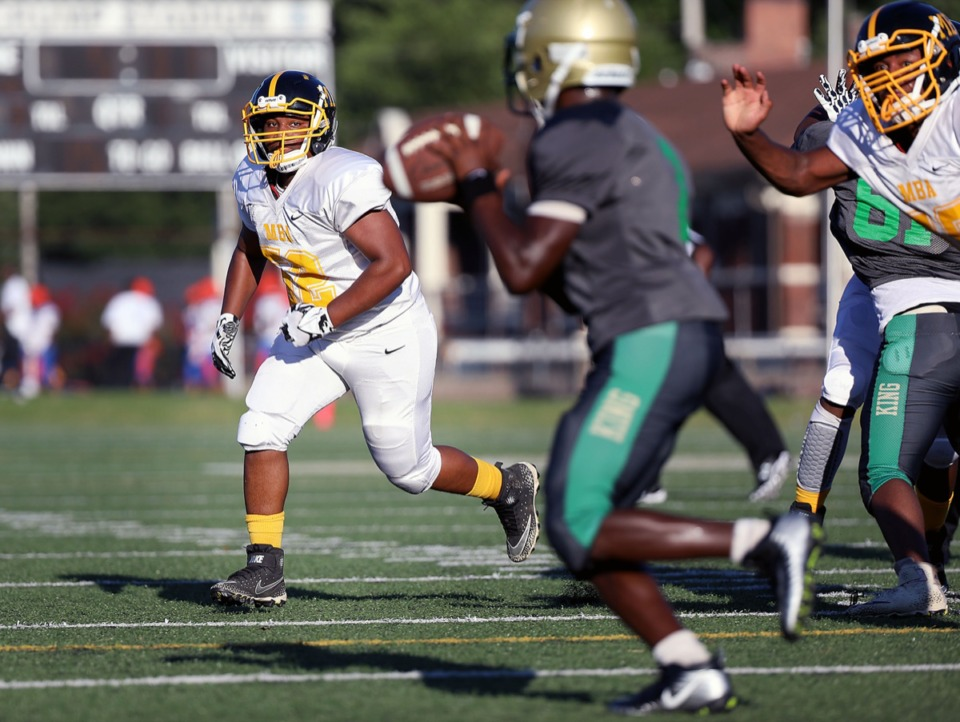 <strong>MBA defender Joseph Bonds (52) eyes MLK College Prep's quarterback Jamerion Caldwell (2) moments before the latter is sacked during the Shelby County Interscholastic Athletic Associations' Football Jamboree at Crump Stadium. (</strong>Patrick Lantrip/Daily Memphian)
