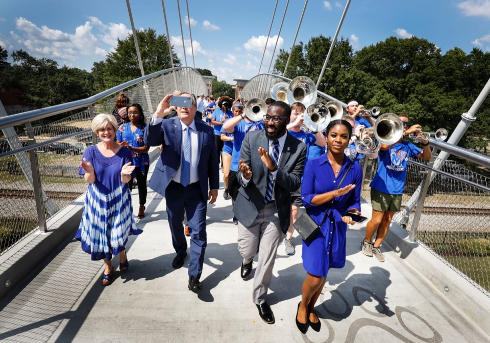 <strong>University of Memphis President David Rudd (second left),&nbsp;SGA President Antonio Scott (middle) and Vice President Desiree Dyson (right) lead a procession of students and faculty members during the first official crossing of the long-awaited pedestrian cable bridge on campus Wednesday, Aug. 21, 2019.</strong> (Mark Weber/Daily Memphian)