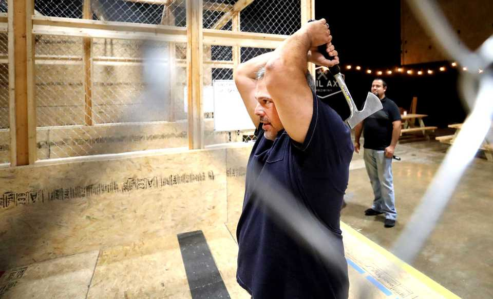 <strong>Mason Jambon throws an axe at a pine target at Civil Axe Throwing on Broad Avenue in Midtown Memphis. The new business, located near the Rec Room, allows customers to compete in axe throwing competitions.</strong> (Hosuton Cofield/Daily Memphian)