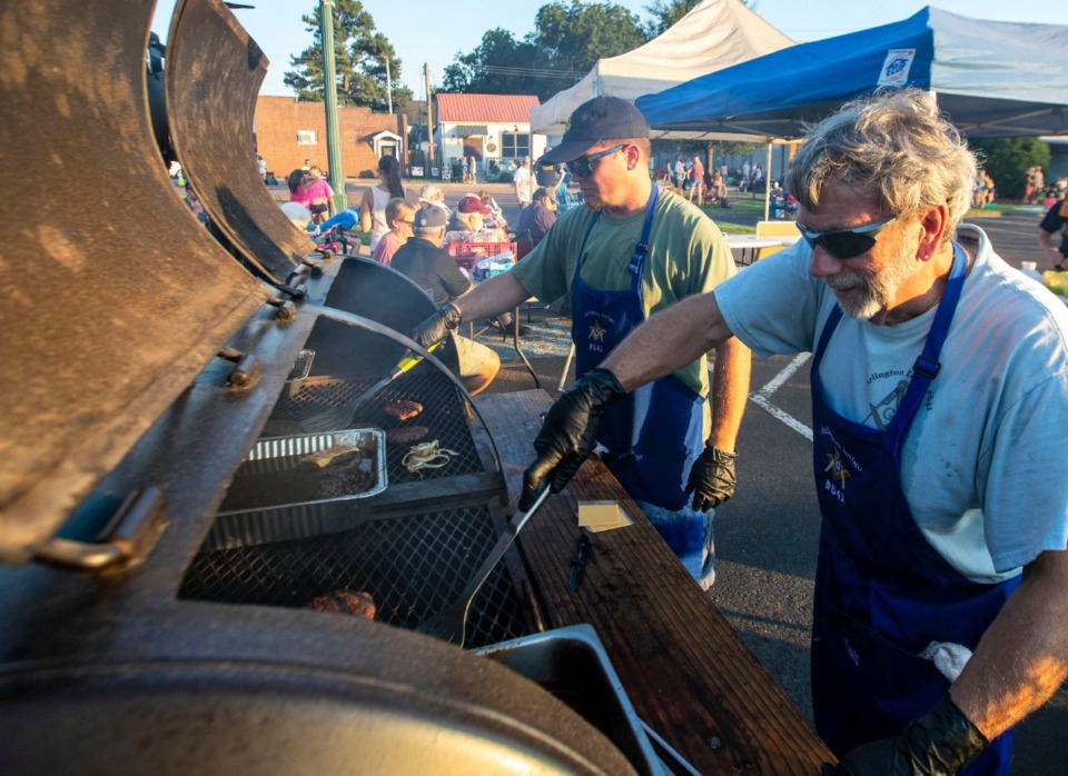 <strong>Gary Baker, left, and Ricky Coats keep the hamburgers grilling as Arlington-area residents attend the town's Music On The Square concert Aug. 17, 2019.</strong> (Mike Kerr/Special to The Daily Memphian)