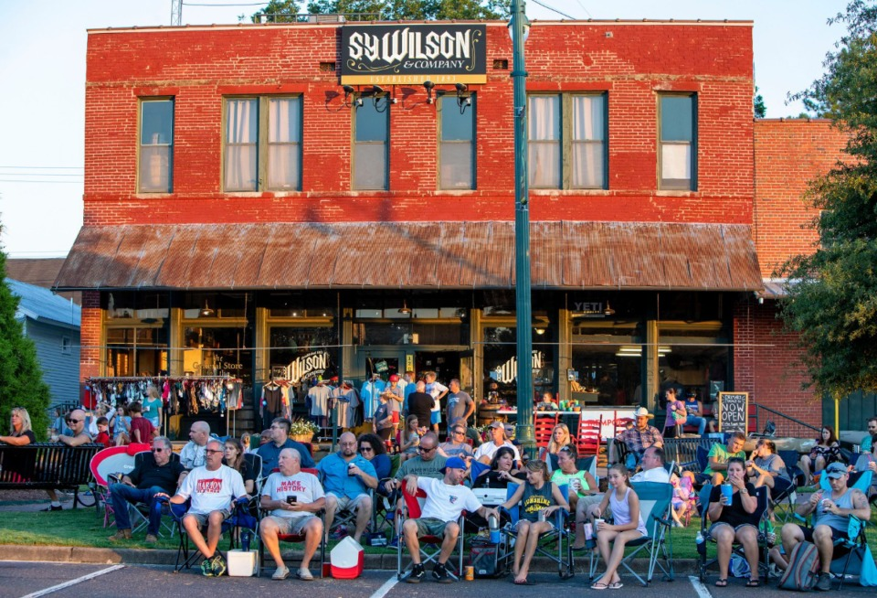 <strong>The S.Y. Wilson and Company storefront provides the backdrop as a crowd listens to music by Memphis band Area 51 during Arlington's Music On The Square series Aug. 17, 2019.</strong> (Mike Kerr/Special to The Daily Memphian)