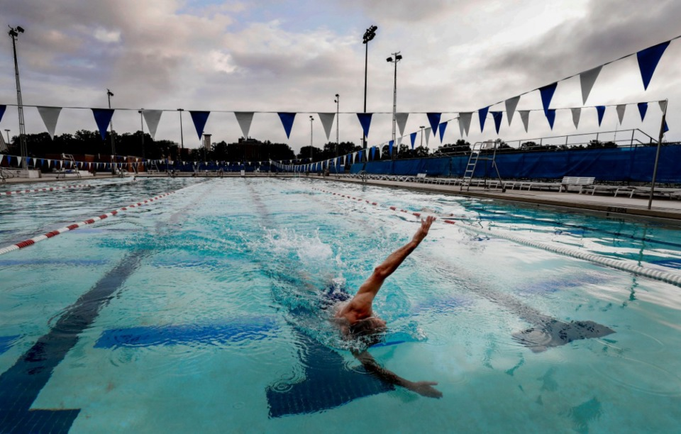 <strong>Jack Leake, 71, finishes his final laps at the University of Memphis outdoor pool just before dawn Friday, Aug. 23. For years the pool has hosted the Early Bird swimmers, a group of Memphians ages 40s and older who swim every morning at the pool. The 50-meter pool will be demolished in the coming weeks as the university makes way for redevelopment that will include renovation of the existing rec center along with a new center.</strong> (Mark Weber/Daily Memphian)