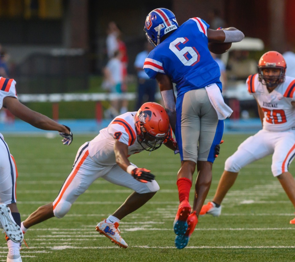 <strong>Ridgeway sophomore Quintarrius Ayers (center, in orange) tackles MUS wide receiver Roderic Lewis &nbsp;(6) in the open during Friday night's contest at MUS.</strong> (Greg Campbell/Special to the Daily Memphian)