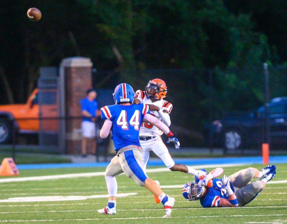 <strong>Ridgeway quarterback Anterrion Martin (in orange) releases the ball as MUS's Elliot Allen hangs on to his foot and Robert Dickinson (44) pursues him Friday night at MUS.</strong> (Greg Campbell/Special to the Daily Memphian)