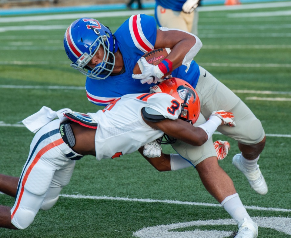 <strong>MUS running back Hunter Kendall (with ball) fights for extra yards as Ridgeway safety Nicholas Terrell tackles him on their own 20-yard line.</strong> (Greg Campbell/Special to the Daily Memphian)