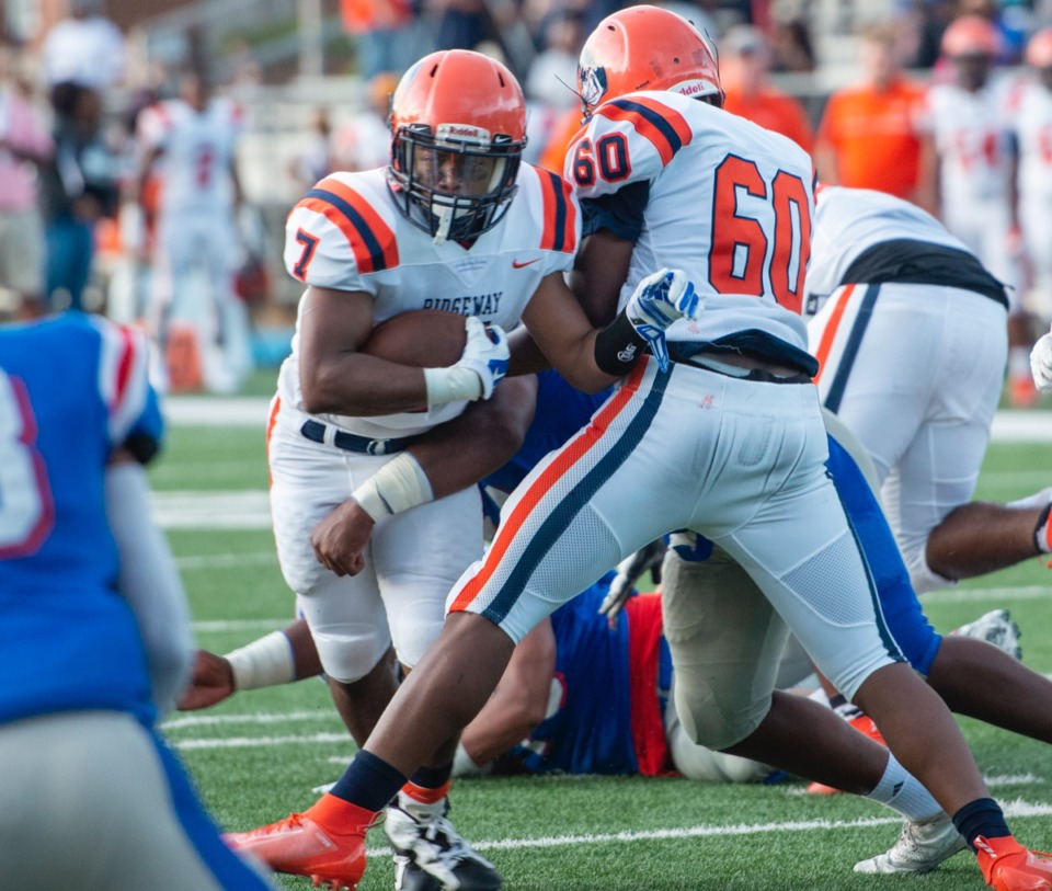 <strong>Ridgeway running back Brandon Goodwin fights through the line as teammate Dearrius Majors helps block MUS defenders during Friday night's game at MUS.</strong> (Greg Campbell/Special to the Daily Memphian)