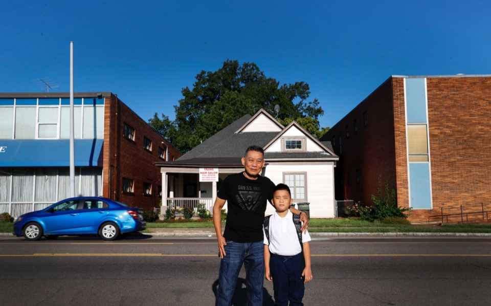 <strong>Lee Nguyen and his son Huy, 7, stand in front of their modest home on North Cleveland Thursday, Aug. 29. Recently, the family received approval from the Board of Adjustment to create two parking spaces in the front yard.</strong> (Mark Weber/Daily Memphian)