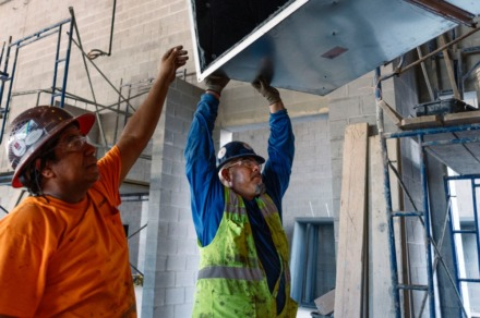 <strong>Jose´ Meza (left) and Juan Cortez lift an HVAC unit to be installed in Bartlett High School's new cafeteria. The $60 million transformation of the campus, which began in the summer of 2017, is the school's first expansion in 40 years.</strong> (Houston Cofield/Special to Daily Memphian)