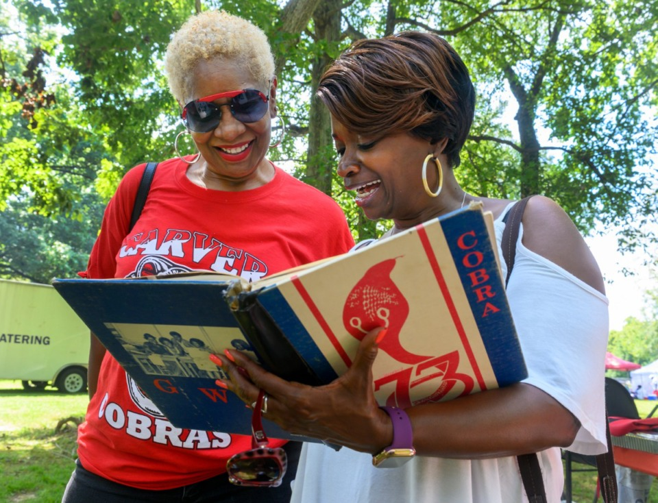 <strong>Jernetha Fleming, left, Carver High School class of 1973, looks at her old high school yearbook with friend, Rita Ayers, at the Carver High School all class reunion at Martin Luther King park Saturday.</strong> (Greg Campbell/Special to The Daily Memphian)