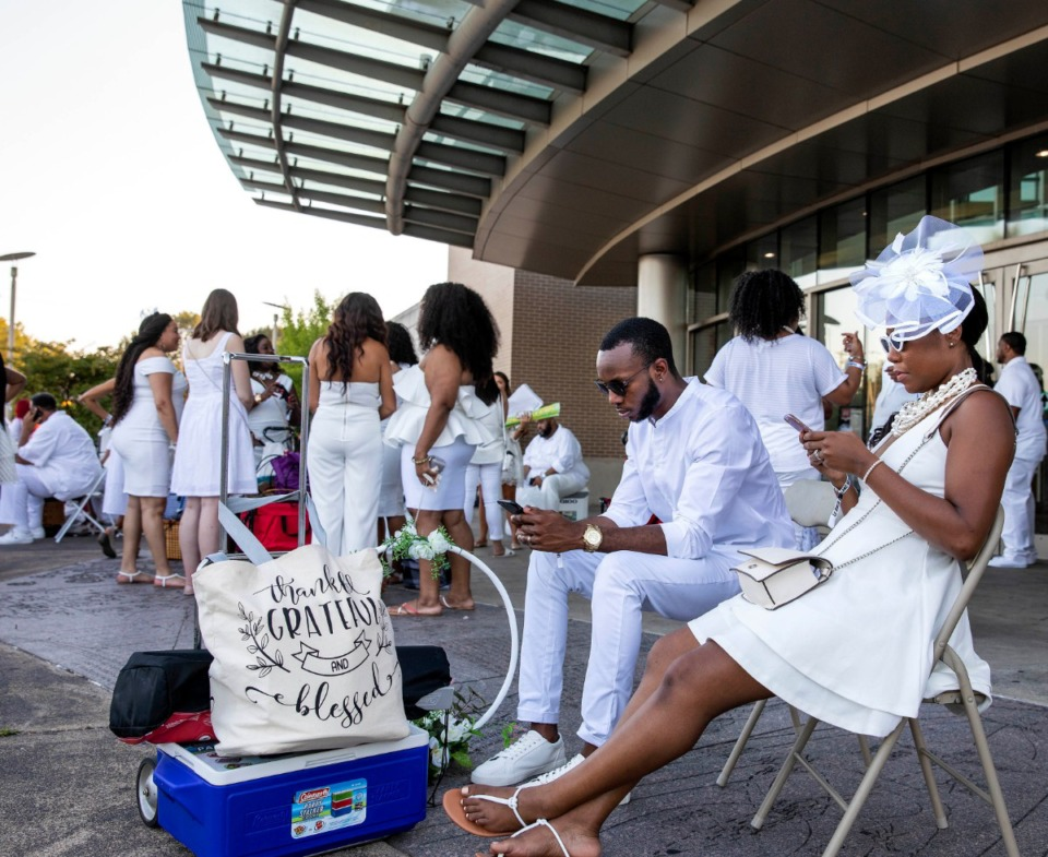 <strong>Justin and Janessa Johnson check their phones as they wait to be transported by chartered bus to the Diner en Blanc. They were among a crowd of close to 100 who waited for more than an hour at a pre-arranged pickup point outside Benjamin L. Hooks Central Library. The first bus arrived about 7:15 p.m.</strong> (Mike Kerr/Special to Daily Memphian)