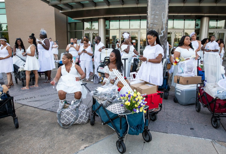 <strong>About 100 people waited for more than an hour Saturday outside Benjamin L. Hooks Central Library to be transported by chartered bus to the Diner en Blanc.</strong> (Mike Kerr/Special to Daily Memphian)