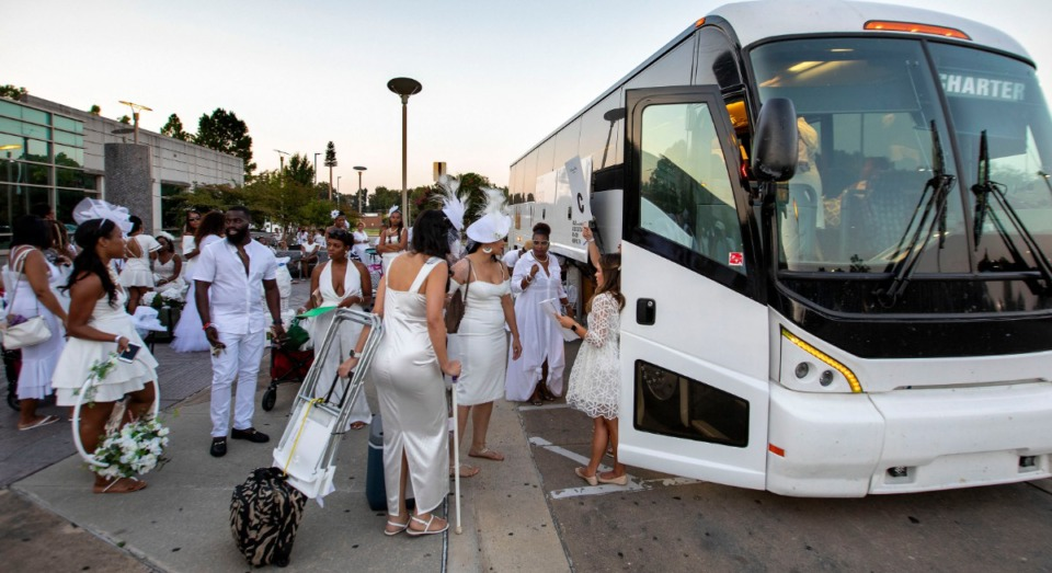 <strong>White-clad participants carrying white table accessories board a charter bus Saturday evening. The buses take participants to a destination --- in this case, Civic Center Plaza Downtown --- that is a secret until they arrive.</strong> (Mike Kerr/Special to Daily Memphian)