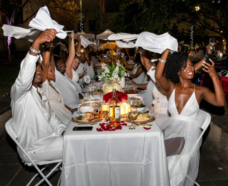<strong>White linen napkins are whirled in the air to the music as those attending the second annual Diner en Blanc dance.</strong> (Mike Kerr/Special to Daily Memphian)