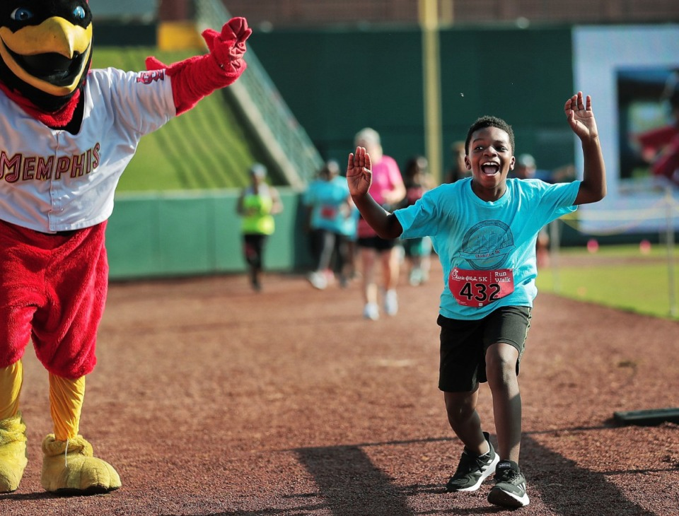 <strong>Michael Lowe, 10, flaps along with Rocky the Redbird on the final stretch as he finishes the 17th Annual Chick-fil-A 5K at AutoZone Park benefiting Junior Achievement on September 2, 2019.</strong> (Jim Weber/Daily Memphian)