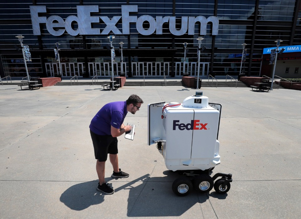 <strong>Richard DiPasquale, a member of the FedEx SameDay Bot test team, checks systems on Roxo before starting a test run in front of the FedExForum. FedEx is testing Roxo this month Downtown and in the Poplar Plaza area.</strong> (Jim Weber/Daily Memphian)