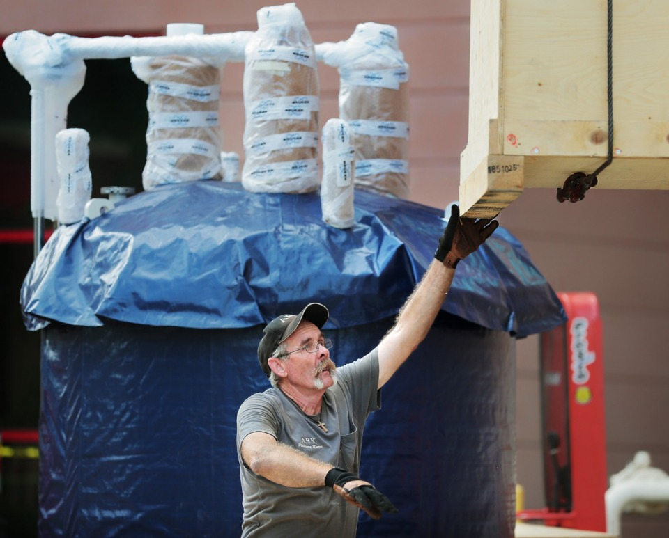 <strong>Rigging specialist John Harding guides a box of equipment away from a giant magnet as it is lifted into St. Jude's Kay Research and Care Center on the St. Jude campus on Sept. 5, 2019. Workers at the research hospital worked all morning to place the $10 million magnet, the largest of its kind in the world, which will help the hospital look deeper into cells.&nbsp;</strong>(Jim Weber/Daily Memphian)