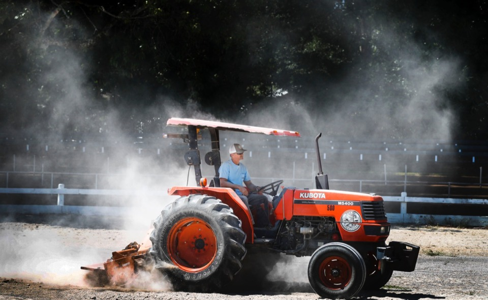 <strong>City of Germantown employee Anthony German creates a dust cloud while mowing weeds and leveling the arena ground Thursday, Sept. 5, before this weekend's Germantown Festival.</strong> (Mark Weber/Daily Memphian)