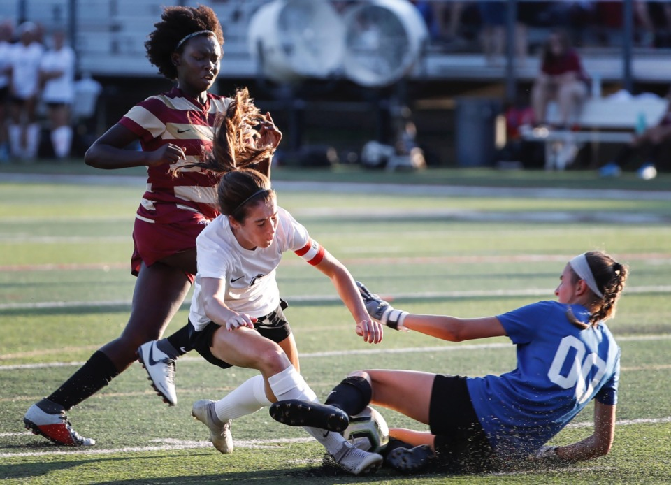 <strong>ECS goalie Bryn Todd (right) knocks the ball away from charging Houston forward Madeline Eskin (middle) as defender Kanny Kumtor (left) assists Thursday, Sept. 5.</strong> (Mark Weber/Daily Memphian)
