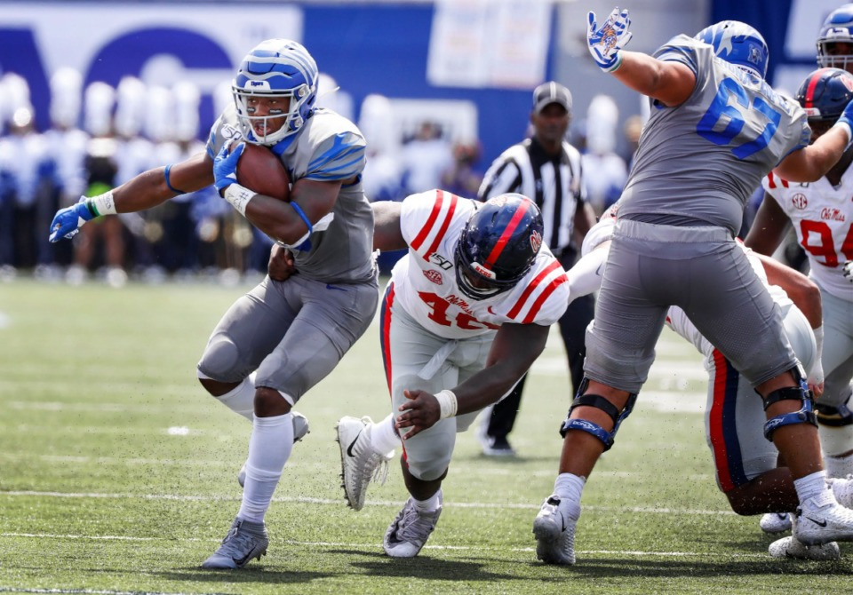 <strong>Memphis running back Kenneth Gainwell (left) scrambles past the Ole Miss defensive line for positive yards during action in their NCAA football game at the Liberty Bowl Memorial Stadium on Aug. 31, 2019.</strong> (Mark Weber/Daily Memphian)