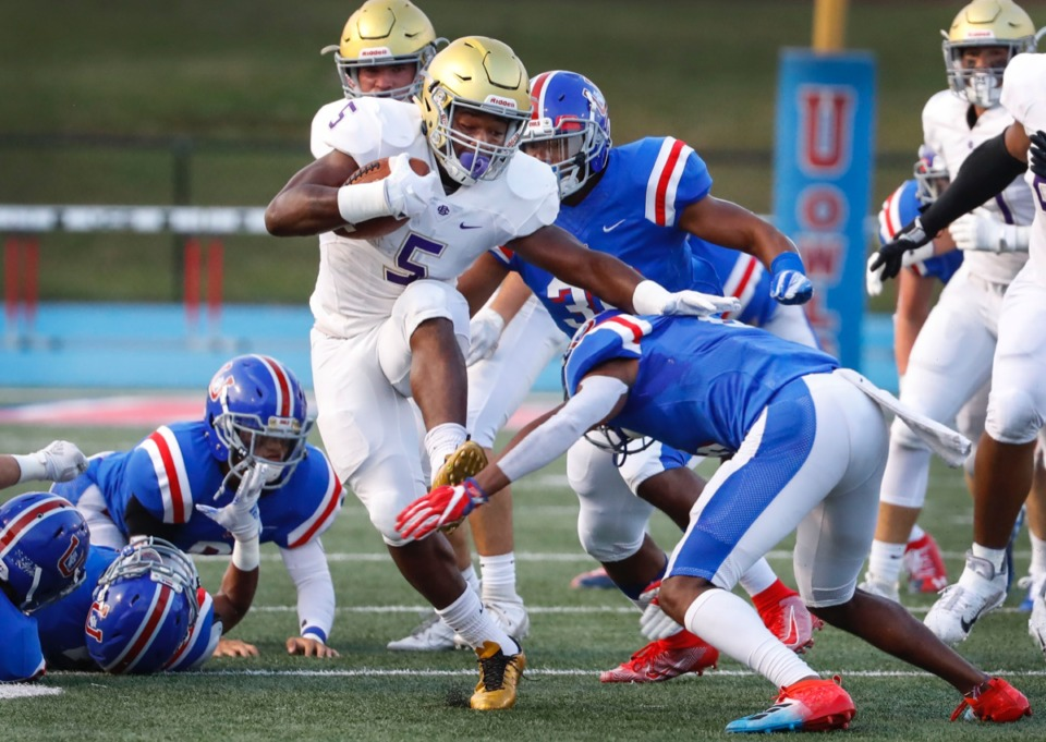 <strong>CBHS running back Al Wooten (middle) is brought down by MUS defender Cody Hopkins (right) Friday, Sept. 5.</strong> (Mark Weber/Daily Memphian)