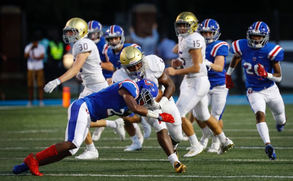 <strong>CBHS' Al Wooten (center, with ball) is taken down while returning a kickoff by MUS' DeVonte Nelson (left) Friday, Sept. 5.</strong> (Mark Weber/Daily Memphian)