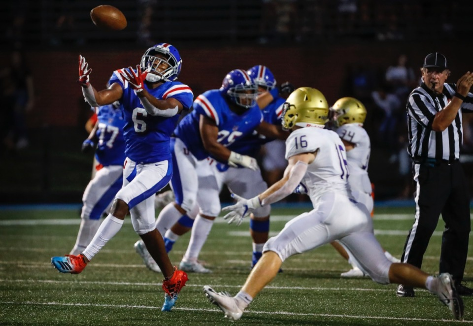 <strong>MUS receiver Roderic Lewis (left) grabs a tipped pass in front of CBHS defender Will Fracchia (center) Friday, Sept. 5.</strong> (Mark Weber/Daily Memphian)