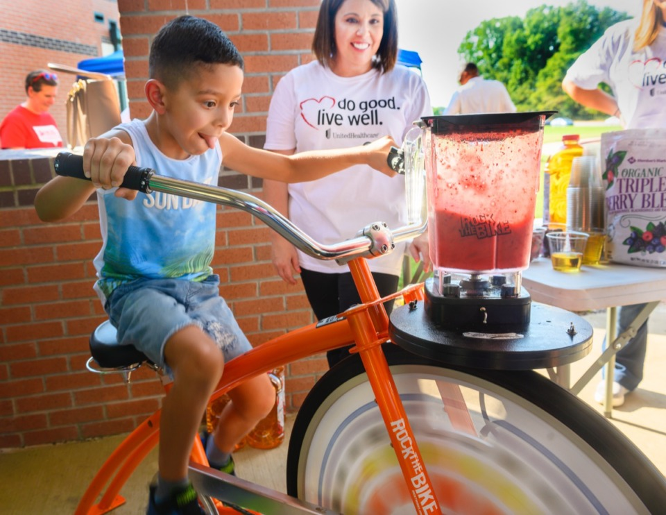 "<strong>Millington Elementary first grader Chris Arredondo pedals to make a smoothie, with the help of UnitedHealthcare's Beth Ross at the ""Y on the Fly"" Sept. 9.</strong> (Greg Campbell/Special to The Daily Memphian)"