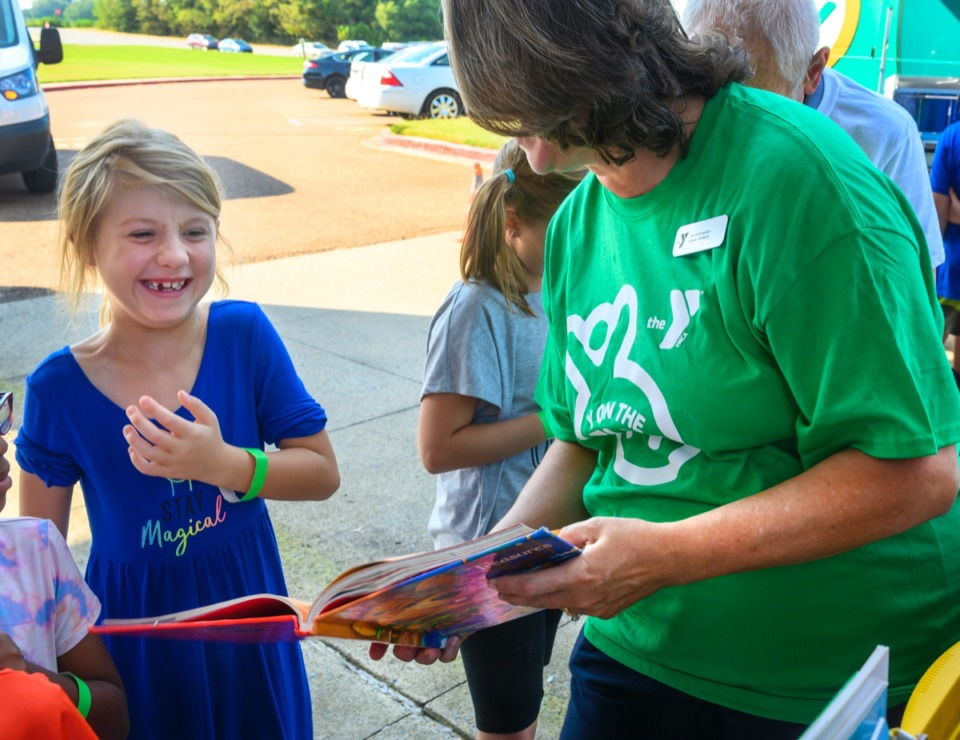 "<strong>Summer Neuenschwanver, left, has a laugh with YMCA's Katherine Wiggs while picking out a book at the ""Y on the Fly"" in Millington Sept. 9.</strong> (Greg Campbell/Special to The Daily Memphian)"