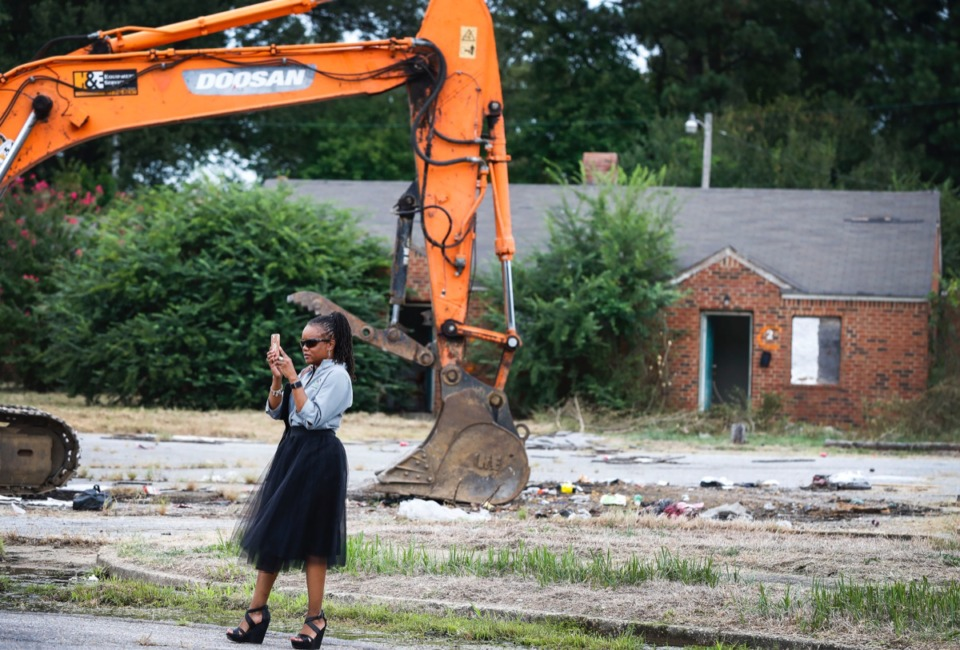 "<strong>Roshun Austin, president and CEO of The Work, Inc., takes a picture while attending a ""Demolition Day"" ceremony as work begins on the vacant Tillman Cove Apartments in Binghampton, Tuesday, Sept. 10.</strong> (Mark Weber/Daily Memphian)"