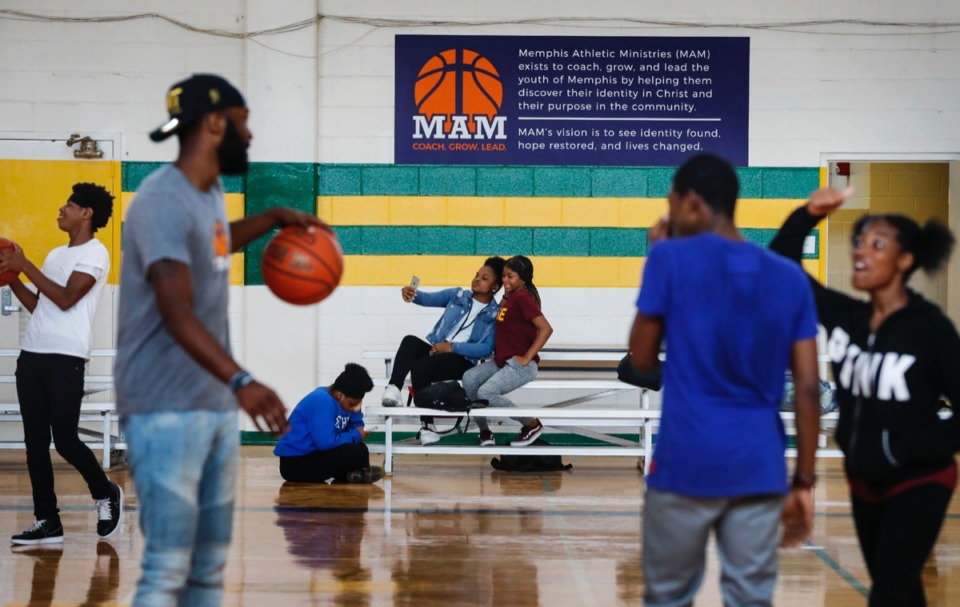 <strong>Jamiyah Wilson, 14 (background, center left), and India Watson, 15 (background, center right), take a selfie while others mingle during a Sept. 11 dedication ceremony for the new community gym at MLK College Prep High School in Frayser.</strong> (Mark Weber/Daily Memphian)