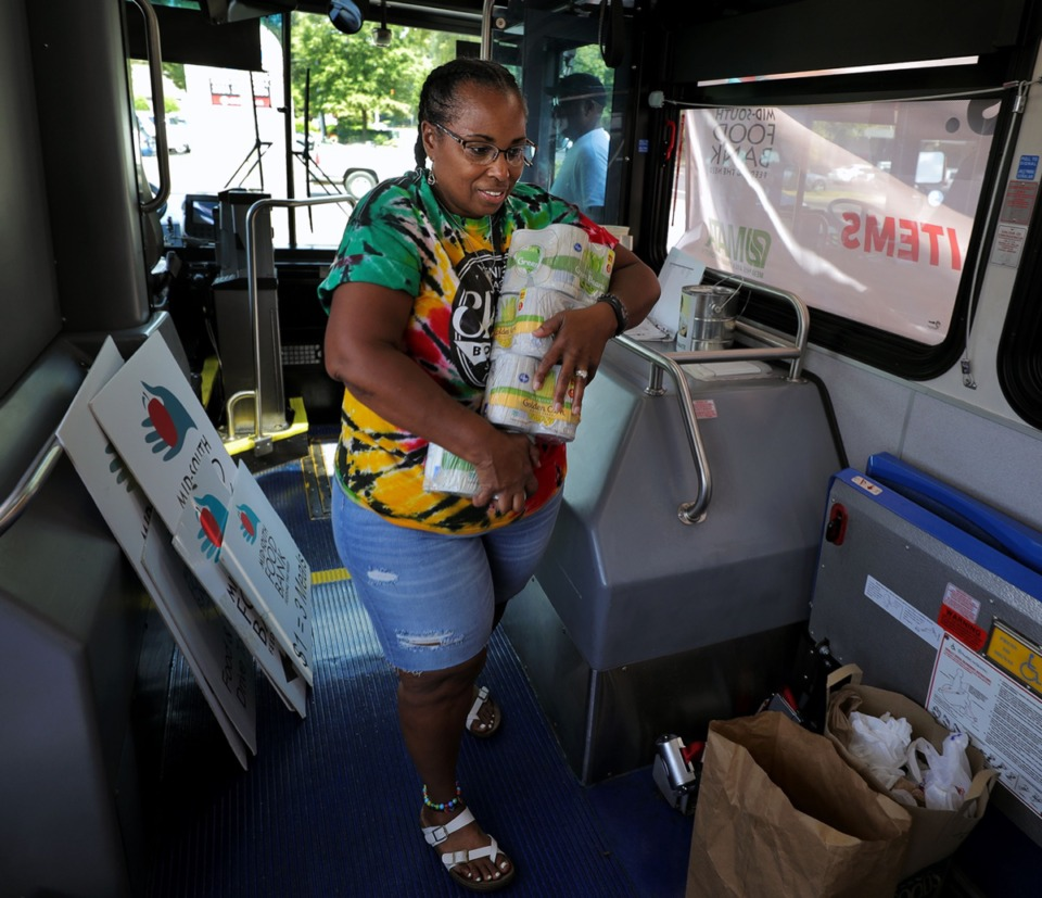 <strong>Donna Daniels-Crawford hauls in an armful of canned corn on Thursday, Sept. 12, 2019, to help fill a MATA bus parked in Poplar Plaza with canned goods for the Mid-South Food Bank.</strong> (Patrick Lantrip/Daily Memphian)