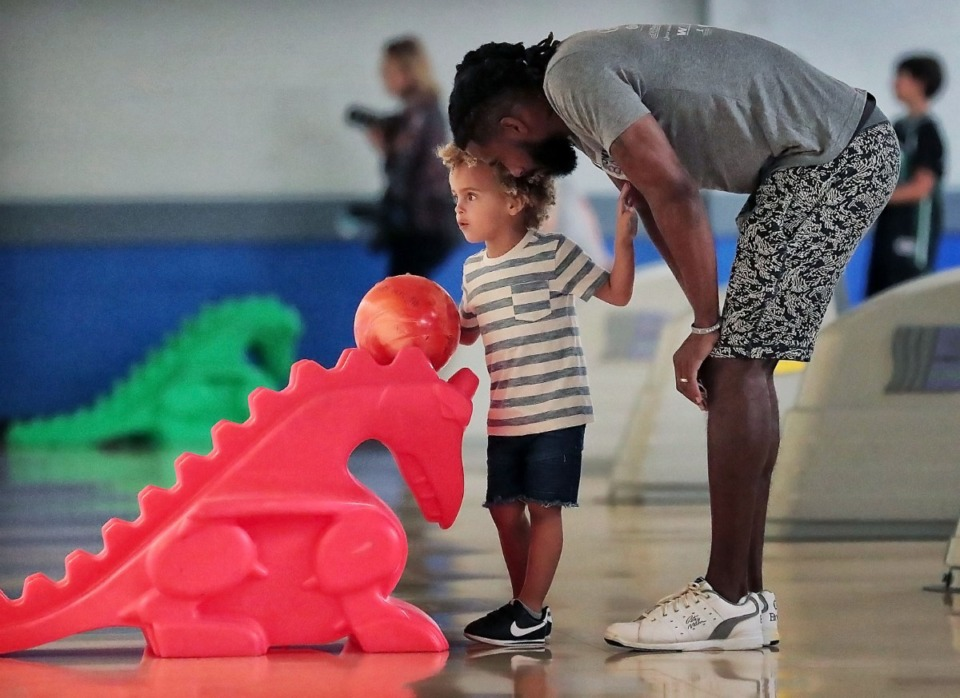 <strong>Former Grizzlies point guard Mike Conley helps his son Myles Conley line up a frame during his annual Bowl-n-Bash charity event at Billy Hardwick All-Star Lanes on Sept. 14, 2019, to raise money for the Methodist Comprehensive Sickle Cell Center.</strong> (Jim Weber/Daily Memphian)