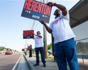 <strong>Michael Foster (right to left), Chris Otis, Dr. Carnita Atwater and Calvin Atwater flash signs as drivers pass in front of Memphis mayoral candidate Willie Herenton's electoral base in South Memphis on Sept. 14, 2019.</strong> (Ziggy Mack/Special to The Daily Memphian)