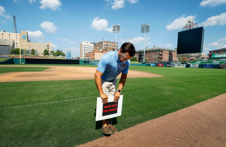 "<strong>Brian Bowe, director of field operations at AutoZone Park, places a ""Stay Off The Grass"" sign near the dugouts Sunday, Sept. 15, 2019. The stadium was upgraded with new turf, after a long combo seasons of Redbirds and 901FC left the old turf with patchy spots.</strong> (Mark Weber/Daily Memphian)"