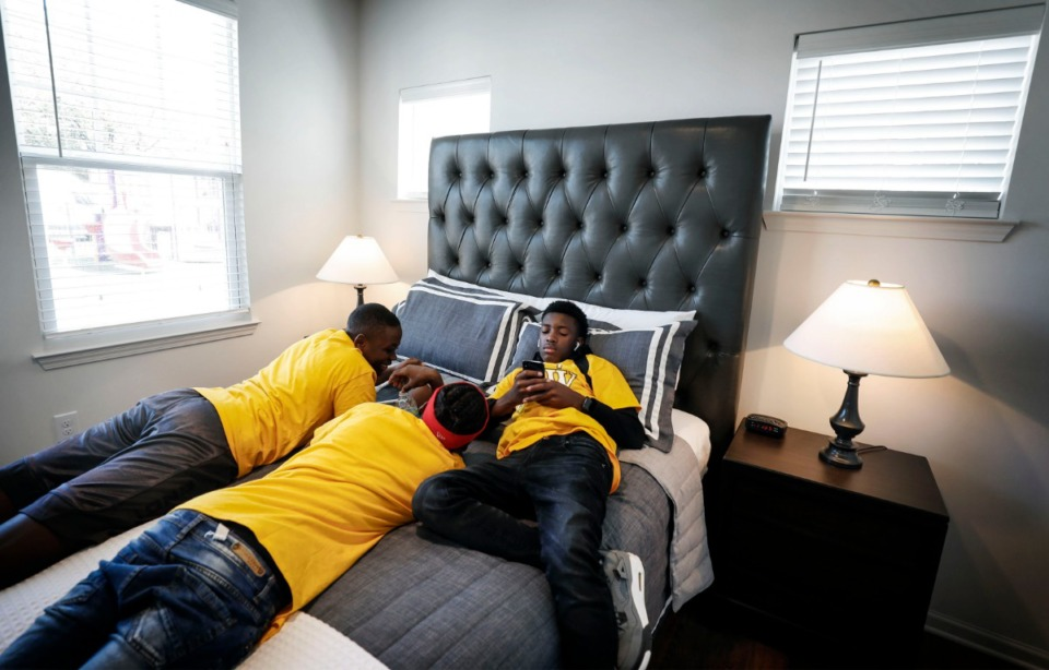<strong>Booker T. Washington High School drum line member Preniago Baines (right) and his bandmates Jamar Frazier (left) and Terrion Fennell (middle) find a cool spot in a model unit during the grand opening of Foote Park at South City Monday, Sept. 16. Baines, his mother and sister will be moving into the newly opened units that have replaced the former Foote Homes public-housing complex.</strong> (Mark Weber/Daily Memphian)