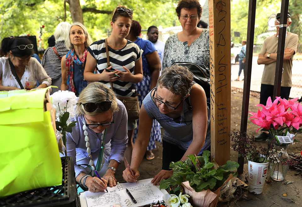 Caitlin Drew looks on as Ruth Boyd and Jules Maxell as sign the guest registry outside of Aretha Franklin's birth home in South Memphis. The three women were part of an Australian gospel choir who happened to be in town while touring with Tony Backhouse, a singer from New Zealand. (Patrick Lantrip/Daily Memphian)