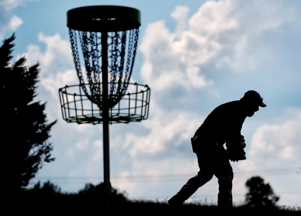 <strong>Lee Biggers with the Arlington Parks and Recreation Department collects disc golf discs at the first basket after a grand opening ceremony on Sept. 12, 2019, for Arlington's newest addition to its parks, the S.Y. Wilson Disc Golf Course, located near the playground at the Arlington Sports Complex.</strong> (Jim Weber/Daily Memphian)