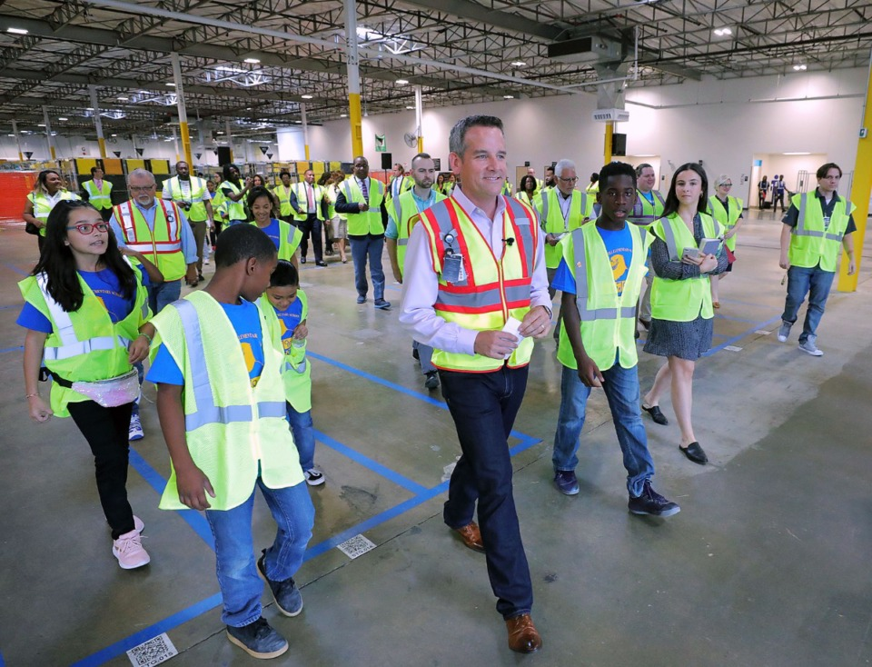 <strong>Accompanied by STEM students from nearby Getwell Elementary School, Amazon regional operations director James Shively leads a short tour of the company's new delivery station at 3347 Pearson. The event Thursday, Sept. 19, was open to the media, government and Greater Memphis Chamber officials and a Shelby County Schools contingent.</strong> (Patrick Lantrip/Daily Memphian)